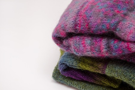 Stack of warm winter knitted sweaters on white background. Handmade concept
