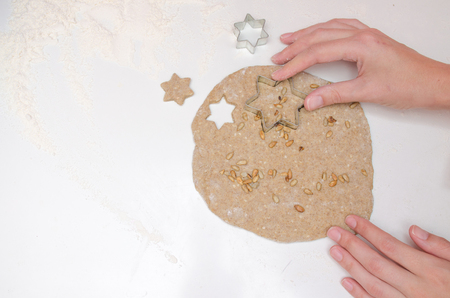 Female hands cut the cookies-stars from rye dough with sunflower seeds on white table Stock Photo