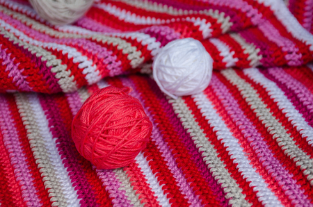 small yarn balls on crocheted striped fabric in red colors . Handmade concept