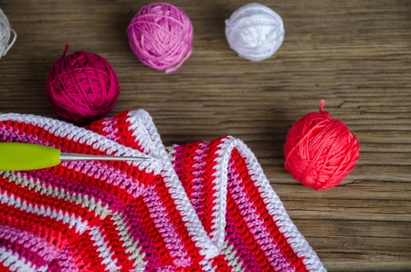 crocheted striped fabric in red colors with crochet hook and many small yarn balls on the old wood background. Handmade concept