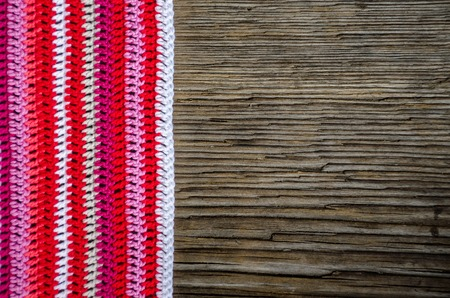 Top view crocheted striped doily in red colors on the old wood background with copy space for your text. Handmade concept