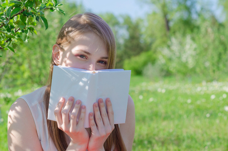 Young pretty woman in white top with long hair sitting under apple tree and hides face behind book on sunny day.