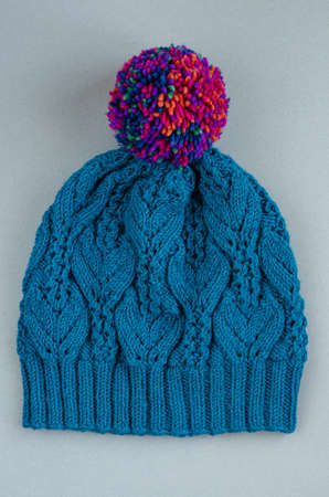 Beautiful two color handknitted hat with pompon on gray background. Top view