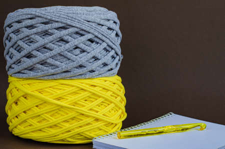 yellow and gray t-shirt yarn balls and yellow crochet hook on notebook on brown background. Craft, handmade, hobby concept.