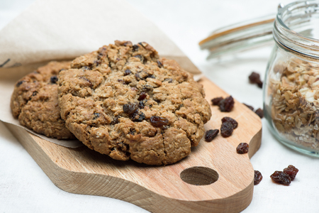 Oatmeal cookie with raisins lying on the Board next to the jar.