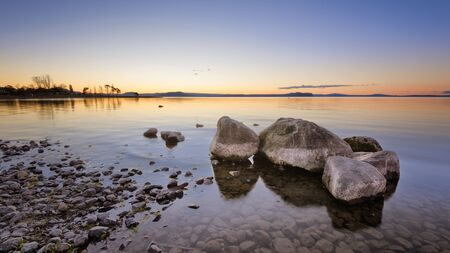 Rocks in the water on Lake Taupo, New Zealand during sunset.