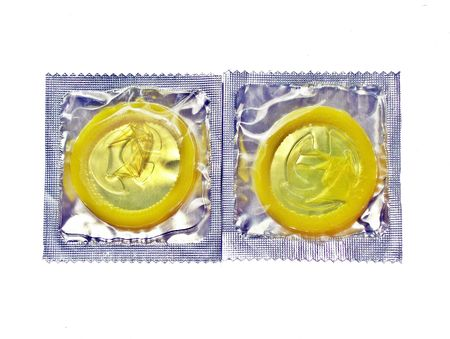condones: Condones de diferentes colores sobre una superficie blanca