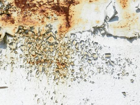 A rusty old metal plate with cracked white gloss paint background photo