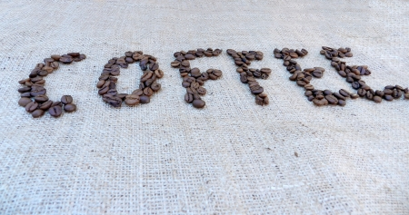 Coffee beans on old burlap background photo