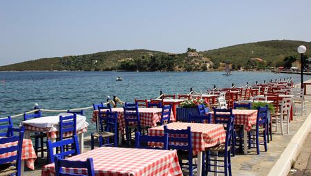 taverna: Greek tavern with wooden chairs by the sea coast, Greece