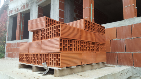 hollow wall: Several red perforated brick on pallet in front of a building under construction