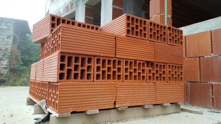 hollow walls: Several red perforated brick on pallet in front of a building under construction