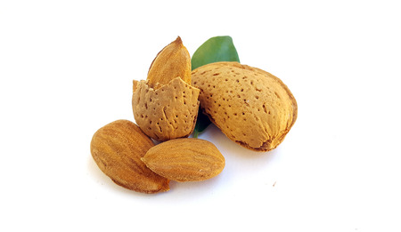 Almonds in their skins and peeled on white background