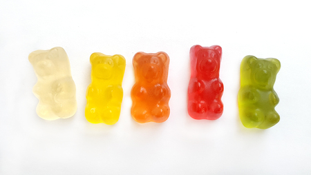 Five fruit gum candy bears in a row on white background