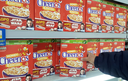 THESSALONIKI, GREECE - February 19, 2018:  A man holding a Cheerios cereals box  in a grocery store.