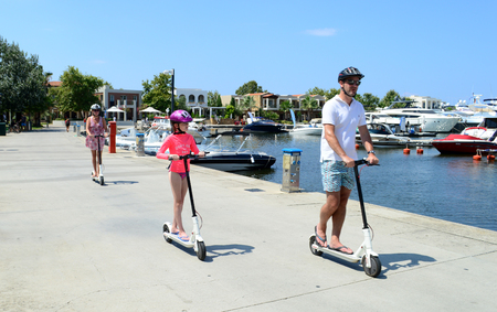 Halkidiki, Greece - July 14 2018: Happy family using electric scooters outdoor on a sunny day