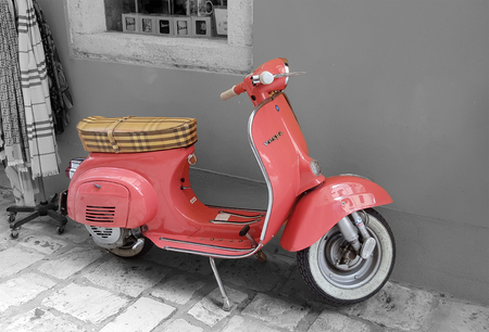 CORFU, GREECE - 17 July 2017. Old pink Vespa scooter on the streets of  Kerkyra, Corfu, Greece.  Black and white. Selective color effect