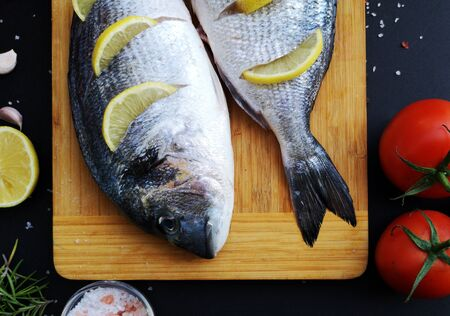 Two ready to cook fresh dorada fish decorated with lemon close-up
