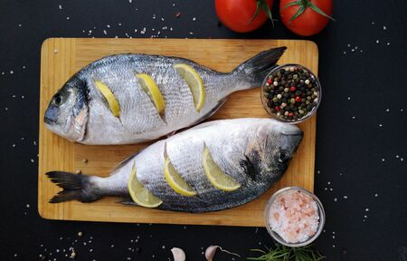Two ready to cook fresh dorada fish decorated with lemon