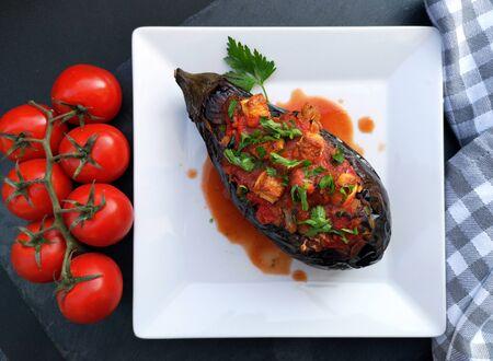Imam Bayildi, traditional turkish food. Eggplant stuffed with vegetables on white plate Stock Photo