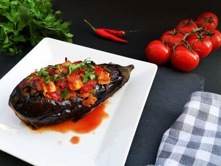 Imam Bayildi, traditional turkish food. Eggplant stuffed with vegetables on white plate