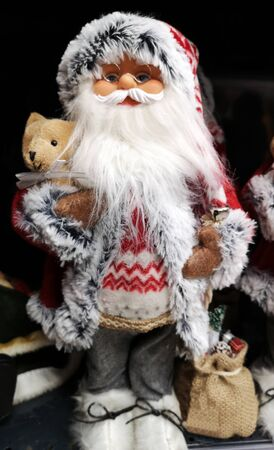 Santa Claus as toy with glasses and holiday costume. Traditional Christmas toy fair.