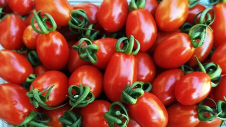 Plum red tomatoes as background
