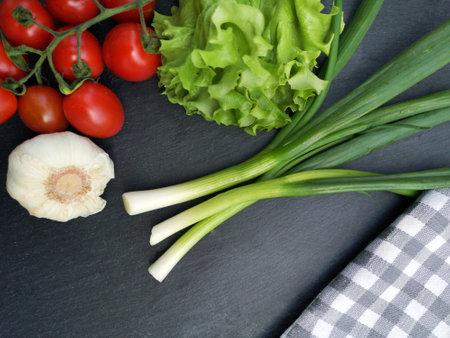 Fresh vegetables ( lettuce, tomato,garlic and green onion ) on dark background