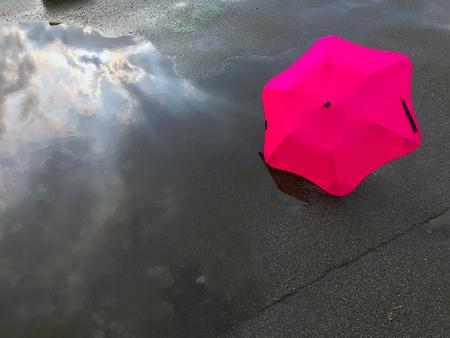 Regenschirm und Reflexion des Himmels in einer Pfütze nach einem Regen Standard-Bild - 87761682