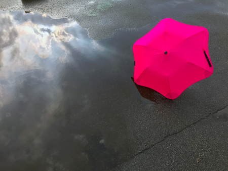 umbrella and reflection of the sky in a puddle after a rain
