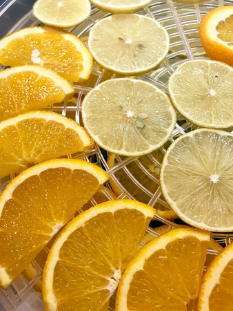 Lemons and oranges cut into slices in drying Stock Photo
