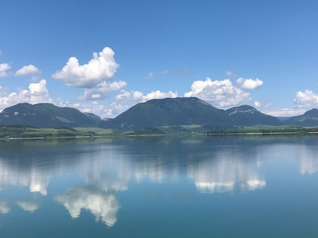 clouds are reflected in the ideal surface of the lake Stock Photo