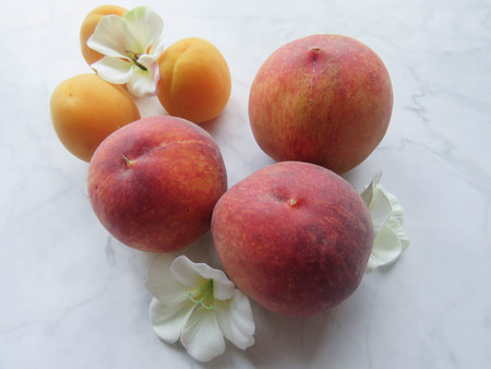 Peaches and apricots lie beautifully on the table