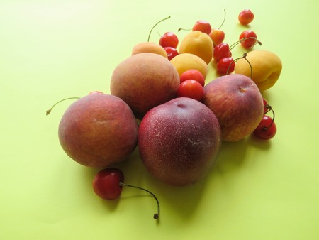 Peaches, apricots and sweet cherries beautifully lie on the table