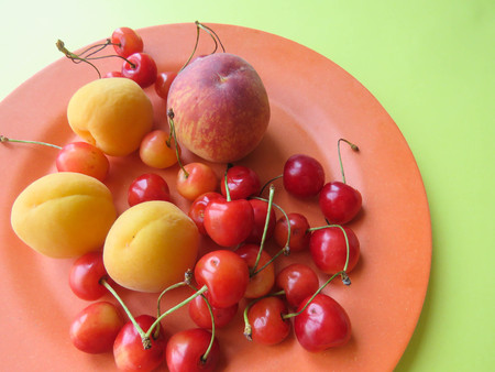 Peaches, apricots and sweet cherries beautifully lie on a plate Stock Photo