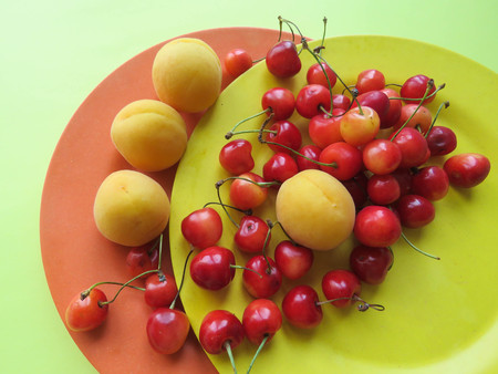apricots and sweet cherries beautifully lie on a plate