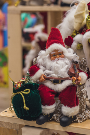 Santa Claus as Toy in red suit costume in a cap and gold-rimmed glasses with a blush on the cheeks carry gifts sale, market, realization in the shop, supermarket Stockfoto