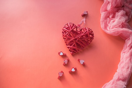 Valentines Day concept. Wicker heart and small clothespins with hearts on a coral background. field for text.