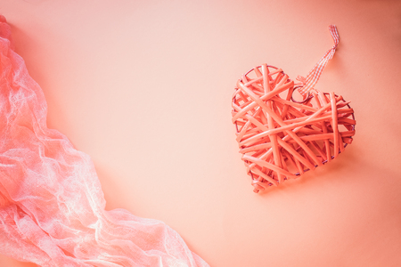 Valentines day concept. Wicker heart on a coral background. field for text. top view 写真素材