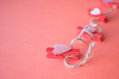 Valentine's Day concept. Small clothespins with hearts on a coral background. field for text. top view 스톡 콘텐츠