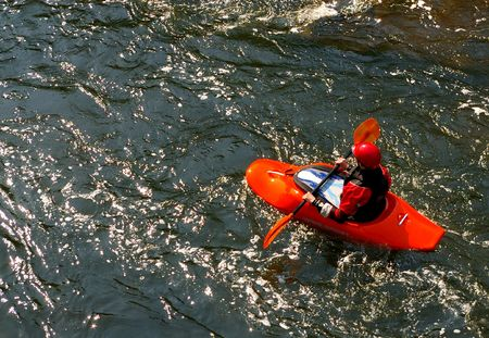 One person floats downwards on the mountain  river in a red boat photo