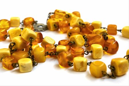 valuables: Necklace from natural amber with a fastener in the form of heart on a white background