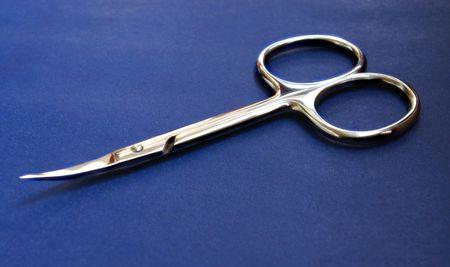 Steel manicure scissors on a  dark blue background photo