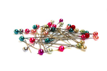 Heap of multi-coloured sewing pins on a white background photo