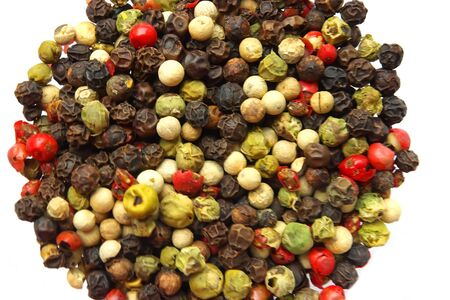 Various kinds of seeds of pepper on a white background photo