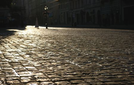 The square of an old European city covered with a wet cobble-stone at the sunrise photo