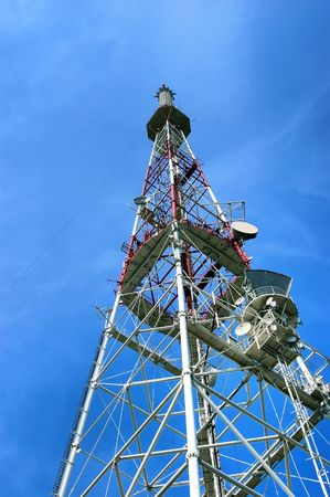 Tower for installation of aerials of cellular communication, on the blue sky background photo