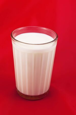 plastik: Glass with fresh milk, on the red background