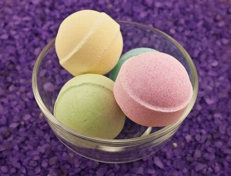 Violet  salt and multicoloured bath balls in glass bowl