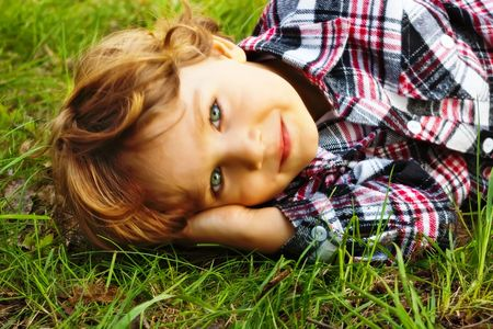 Portrait of a little smiling  boy lying in the grass photo